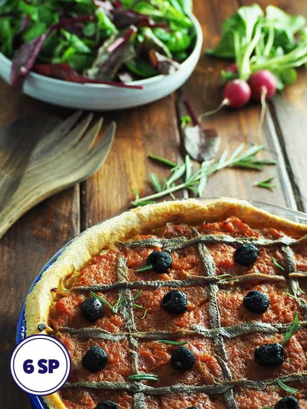 A rustic onion and tomato tart on a table with a bowl of salad
