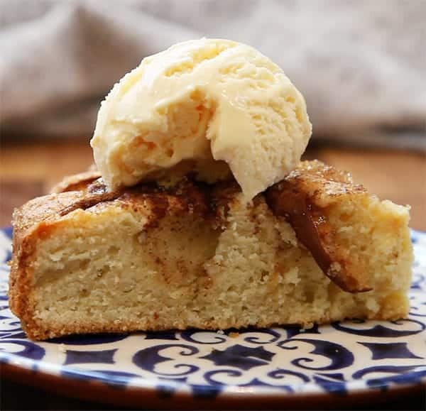 A slice of apple cake on a plate with a scoop of vanilla ice cream