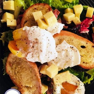 Lyonnaise salad with poached eggs, croutons, bacon and cheese