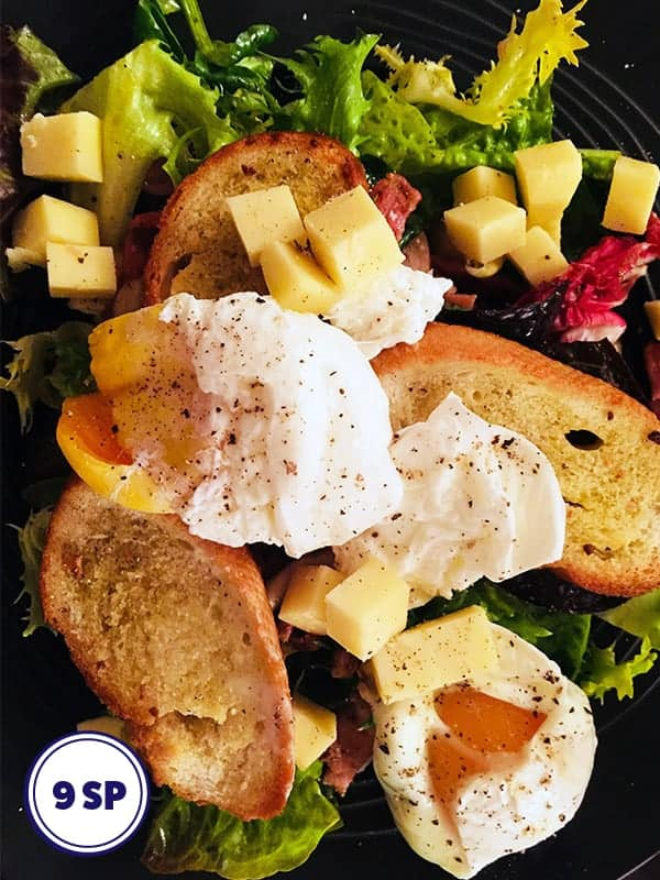 A salad with croutons, cheese and poached eggs.