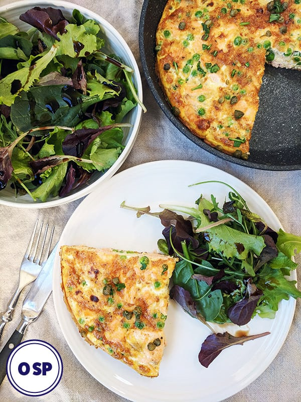 A top down photograph of a salmon frittata on a white plate with salad