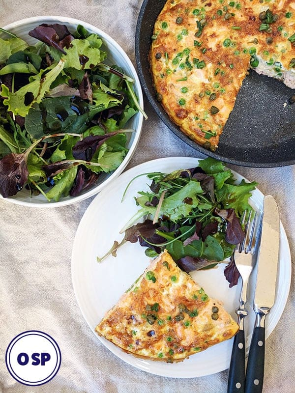 Salmon and Pea Frittata on a white plate with salad