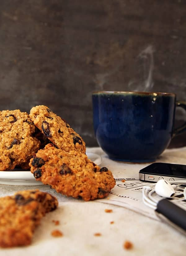 Oat and raisin cookies next to a steaming cup of coffee