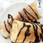 Two banana fritters drizzled with chocolate sauce