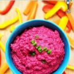 A bright pink beetroot hummus in a blue bowl surrounded by chopped peppers