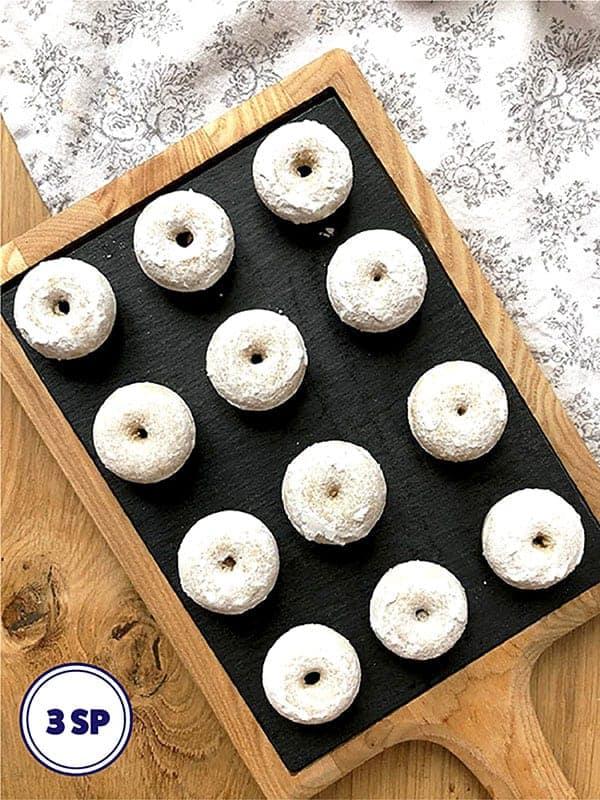 12 mini donuts on a black slate board