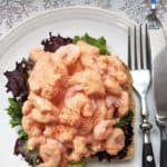 A prawn marie rose open sandwich on a white plate