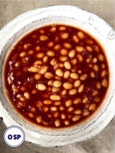 A bowl of baked beans in bbq sauce