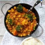 A bowl of chickpea and lentil curry with a bowl of white rice