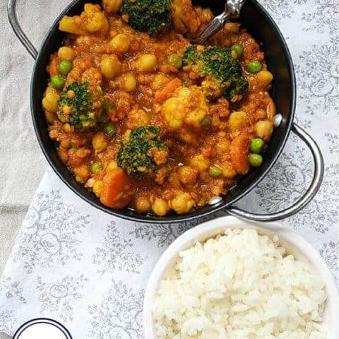 A bowl of chickpea and lentil curry and a bowl of rice