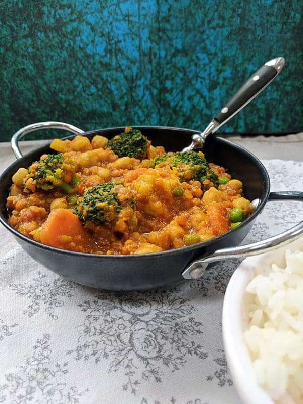 A bowl of chickpea and lentil curry on a white cloth