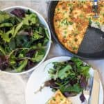 A pan with frittata, a bowl of salad and a plate with frittata and salad
