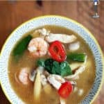 A bowl of tom yum soup on a wooden background