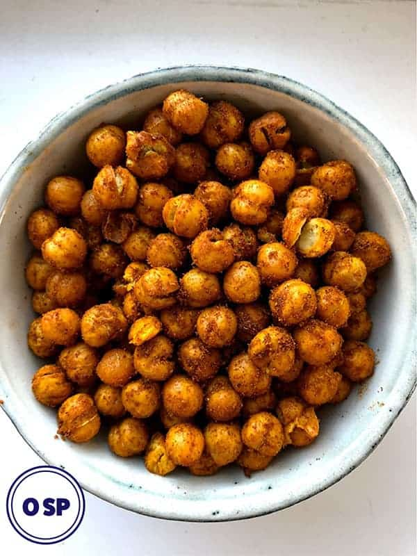 A white bowl full of spice coated roasted chickpeas