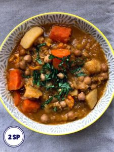 A bowl of vegetable and chickpea broth topped with herbs