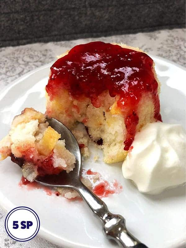A pear sponge topped with raspberry jam on a white plate