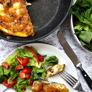 A frittata in a pan with a plate of salad and frittata to the side.