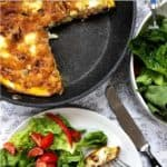 A pan containing frittata on a table with a bowl of salad