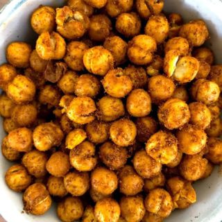 A white bowl full of roasted chickpeas covered in spice