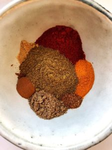 A colorful bowl of shawarma spices