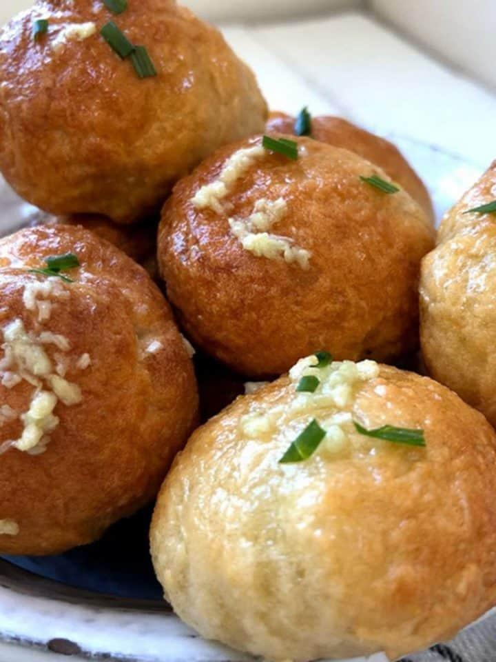 A pile of garlic topped dough balls.