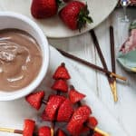 Strawberry kebabs on a board with chocolate dipping sauce