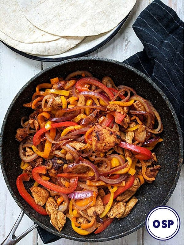 A black skillet of chicken fajita on a white table