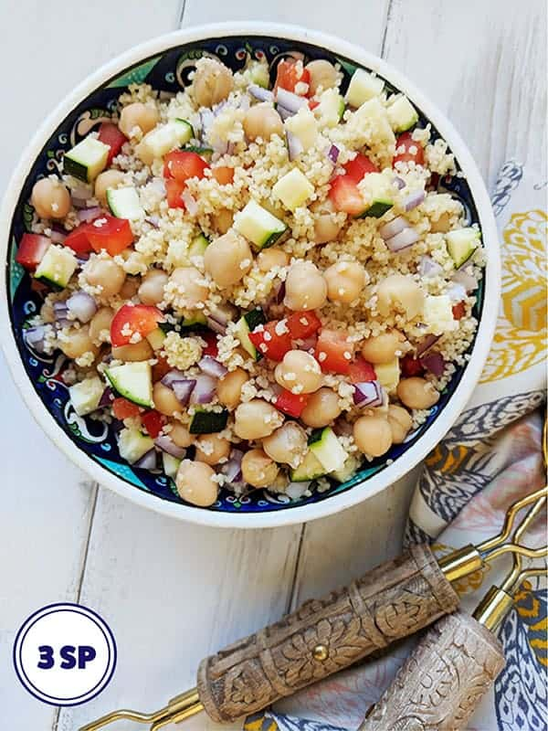 A bowl of couscous salad on a white table