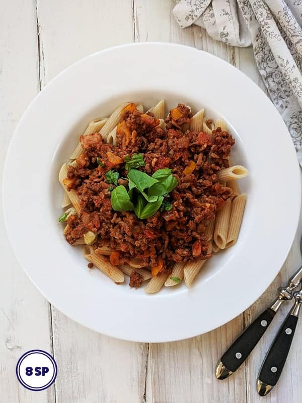 A white bowl of pasta topped with Bolognese sauce