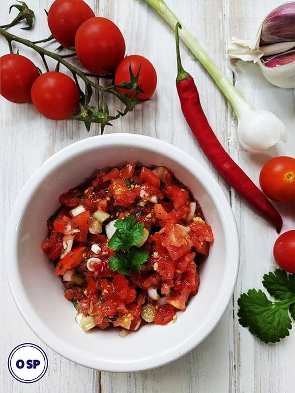 A white dish of salsa with recipe ingredients surrounding it