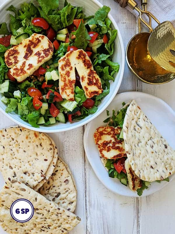 A bowl of salad topped with halloumi cheese
