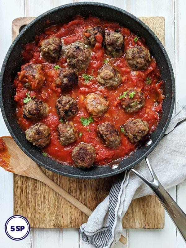A pan of Italian meatballs on a wooden board