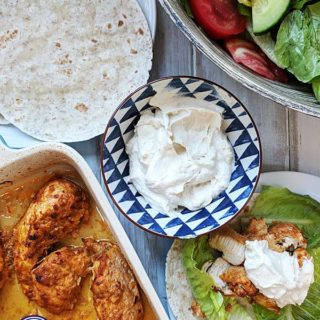 A dish of shawarma chicken with flatbreads and salad