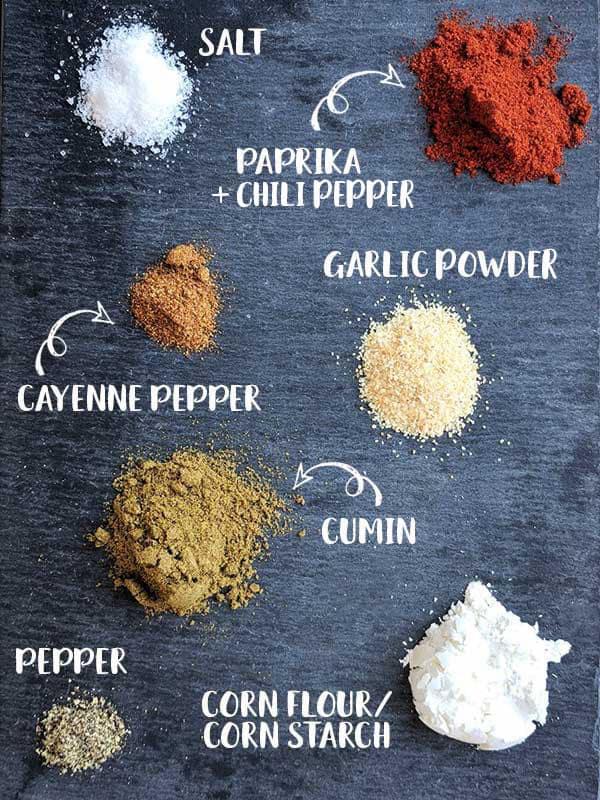 Spices for fajita seasoning mix on a black slate