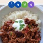 A white bowl filled with chili con carne & rice topped with yogurt and green herbs