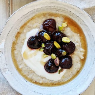 A bowl of porridge with cherries and pistachios