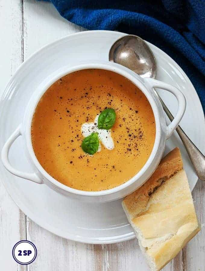 A white bowl of creamy tomato soup with some bread.