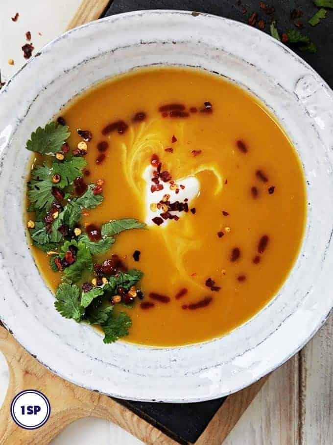A white bowl filled with thai spiced butternut squash soup