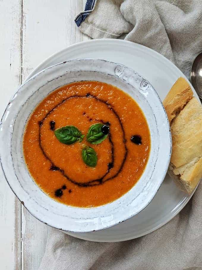 A bowl of tomato soup with a drizzle of balsamic vinegar