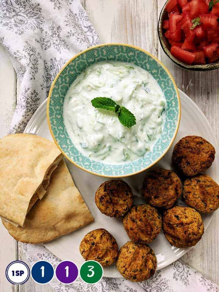 A white plate with falafel, pitta bread and tzatziki