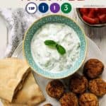 A white plate with falafel and tzatziki