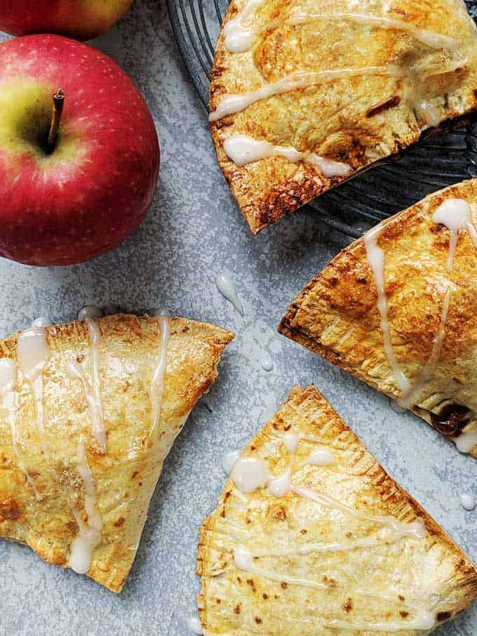 Apple turnovers on a table with a red apple