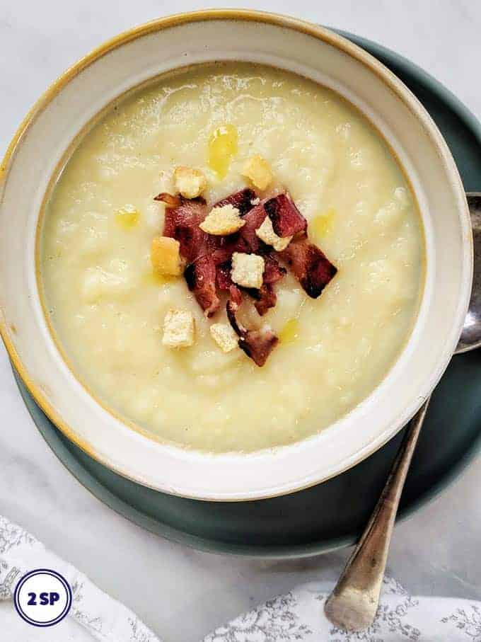 A bowl of celeriac soup topped with crunchy croutons and bacon
