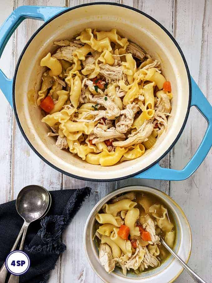 A blue dish of hearty chicken noodle soup
