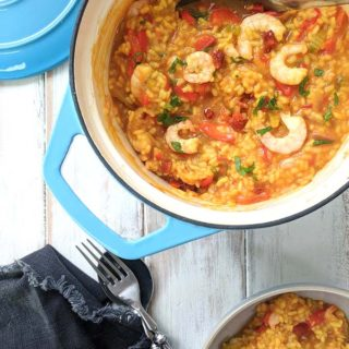 A pot of shrimp, chorizo and red pepper paella on a white table