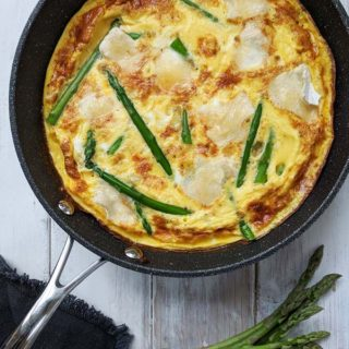 An asparagus and brie frittata on a white table