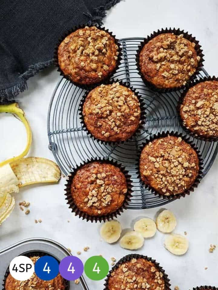 Six banana muffins on a wire rack cooling with banana slices beside them.