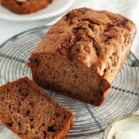 A loaf of Choc Chip Zucchini Bread on a white table
