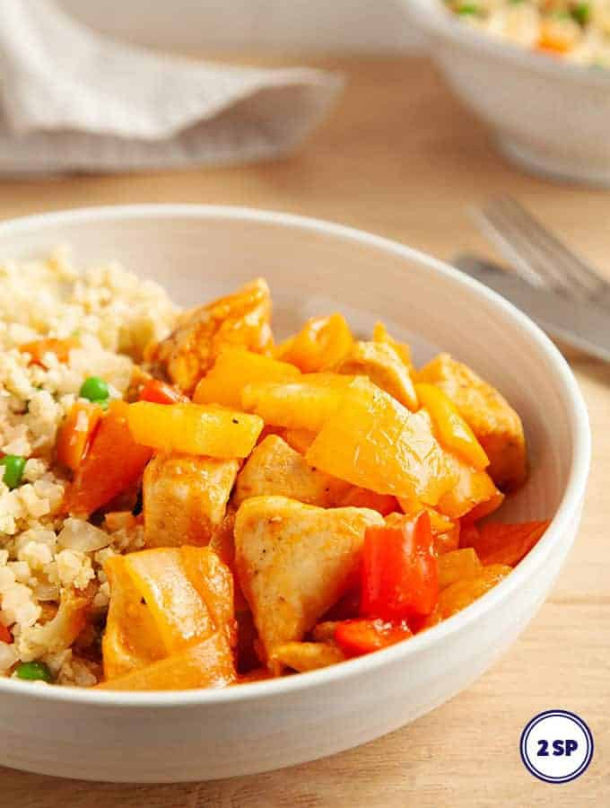 A white bowl full of sweet and sour chicken with egg fried rice