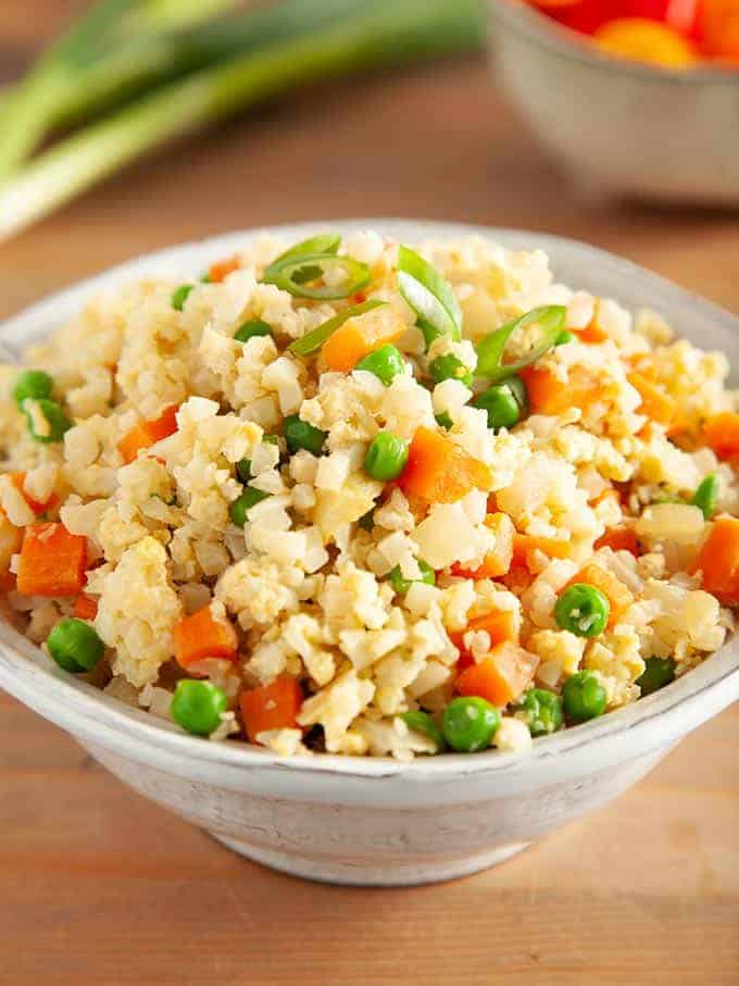 Egg fried cauliflower rice in a white bowl